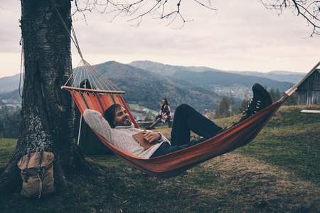 Photo for Handsome young man lying in hammock and smiling while camping with his girlfriend - Royalty Free Image