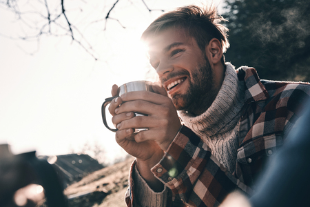 Photo for Handsome young man in warm clothing having morning coffee and smiling while camping in mountains - Royalty Free Image