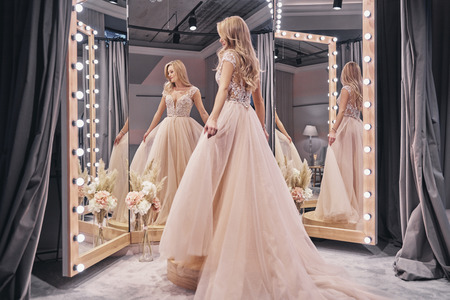 Foto de Beautiful dress.  Full length of attractive young woman wearing wedding dress while standing in front of the mirror in bridal shop - Imagen libre de derechos