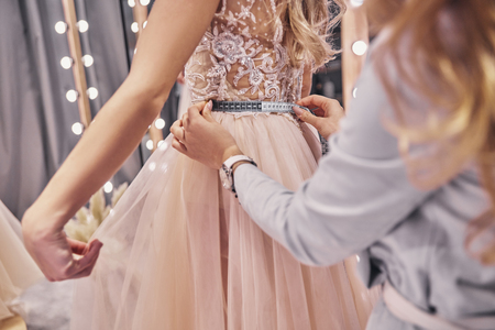 Photo pour Full concentration.  Close up of young woman measuring her girlfriend?s waist while standing in the fitting room - image libre de droit