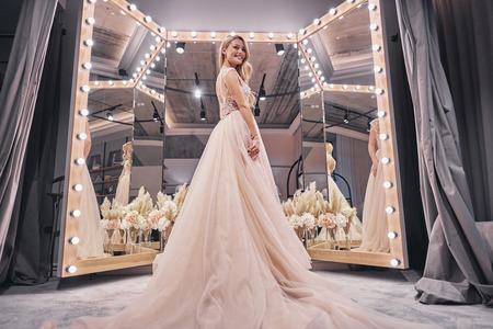 Foto de Exited about her wedding.  Full length of attractive young woman wearing wedding dress and smiling while standing in bridal shop - Imagen libre de derechos