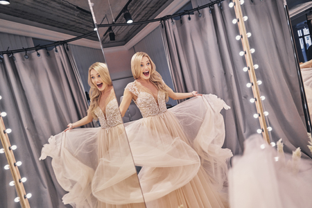 Photo pour Feeling free and happy.  Reflection of beautiful young woman wearing a wedding dress and keeping mouth open while standing in bridal shop - image libre de droit