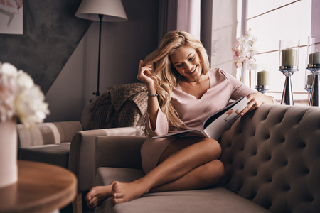 Photo for So interesting. Attractive young woman in elegant dress reading magazine and smiling while sitting on the sofa - Royalty Free Image