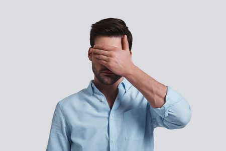 Photo for See nothing.  Handsome young man covering eyes with hands while standing grey background - Royalty Free Image