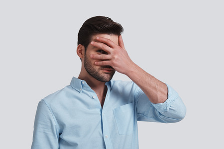 Photo for I want to know everything.  Handsome young man covering eyes with hand and peeking while standing grey background - Royalty Free Image