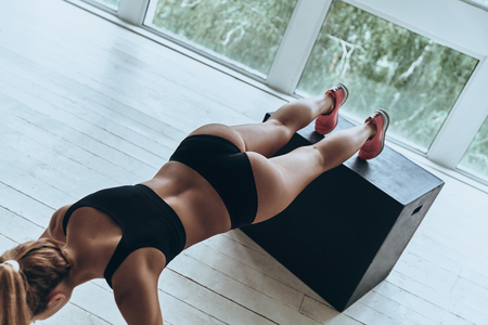 Photo for Working hard to be the best. Top view of young woman in sport clothing keeping plank position while exercising in the gym - Royalty Free Image