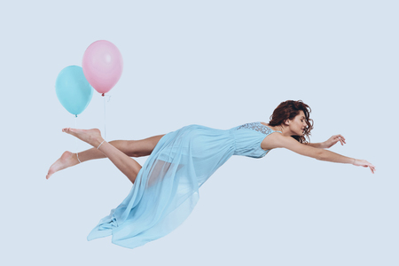 Foto de Dream fly. Studio shot of attractive young woman in elegant dress keeping arms outstretched while hovering against grey background  - Imagen libre de derechos