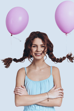 Photo for So cute. Studio shot of playful young woman with balloons tied to her pigtails smiling and looking at camera while standing against grey background      - Royalty Free Image