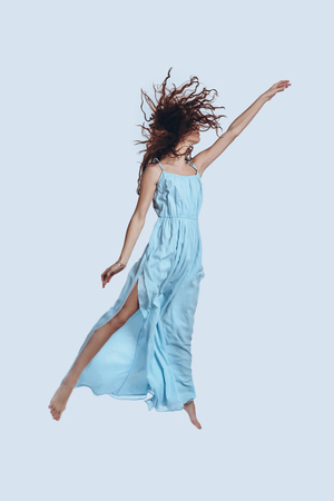 Photo for Magic! Full length studio shot of attractive young woman in elegant dress gesturing while hovering against grey background     - Royalty Free Image