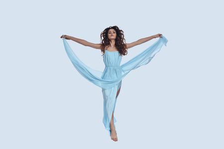 Foto de Perfect beauty. Full length studio shot of attractive young woman in elegant dress gesturing while hovering against grey background - Imagen libre de derechos