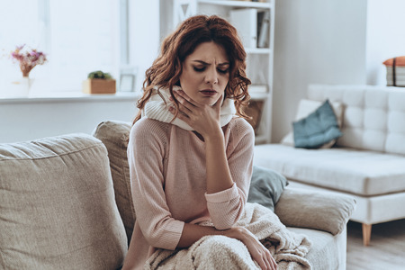 Foto de Being ill. Sick young women covered with blanket coughing while sitting on the sofa at home - Imagen libre de derechos