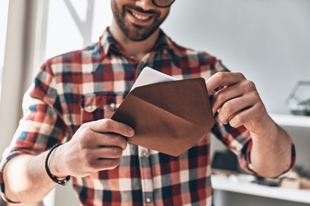Foto de Receiving greeting card. Close up of young man opening envelope and smiling while standing indoors - Imagen libre de derechos