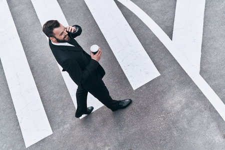 Photo pour Young business professional. Full length top view of young man in full suit talking on the phone while standing outdoors - image libre de droit