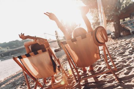 Foto de Summer day. Rear view of two women sunbathing while resting in outdoor chairs on the beach - Imagen libre de derechos