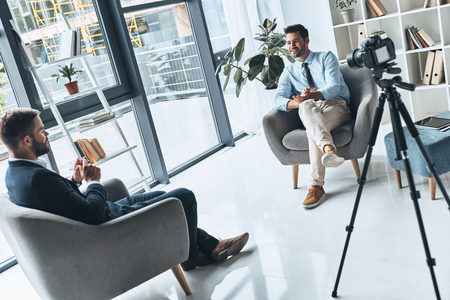 Photo for Business vlog. Two young men in smart casual wear talking while making new video indoors - Royalty Free Image