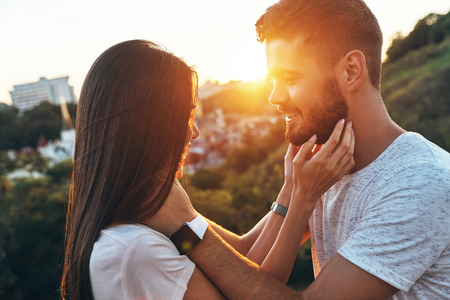 Photo pour Close relationship. Beautiful young couple standing face to face and smiling while spending time outdoors - image libre de droit