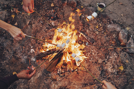 Photo pour Cooking favorite food. Close up top view of young people roasting marshmallows over a bonfire while camping outdoors - image libre de droit