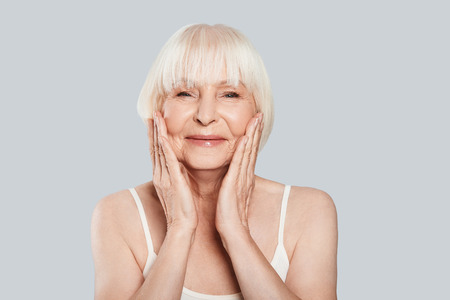 Photo pour Taking good care of her skin. Beautiful senior woman looking at camera and smiling while standing against grey background - image libre de droit