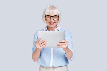 Photo pour Examining her new digital tablet. Beautiful senior woman working using digital tablet and smiling while standing against grey background - image libre de droit