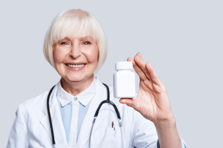 Photo pour New antibiotic. Beautiful senior woman in lab coat holding a bottle with medicines and smiling while standing against grey background - image libre de droit