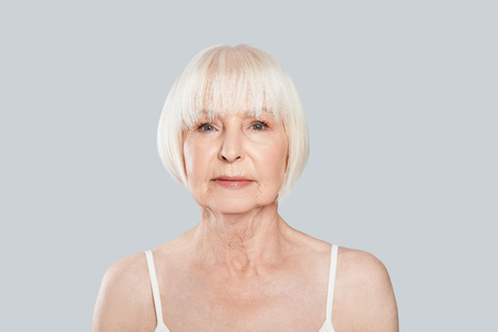 Photo pour Human age. Beautiful senior woman looking at camera while standing against grey background - image libre de droit