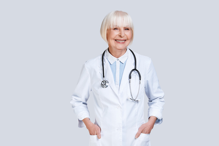Photo pour Healthcare worker. Beautiful senior woman in lab coat looking at camera and smiling while standing against grey background - image libre de droit