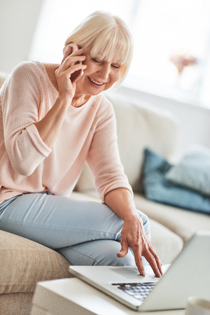 Photo for So good to hear you! Beautiful senior woman talking on her smart phone and smiling while relaxing on the couch at home - Royalty Free Image