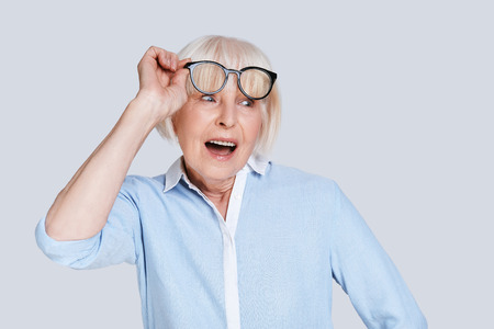 Photo for Unbelievable. Surprised senior woman adjusting eyewear and making a face while standing against grey background - Royalty Free Image