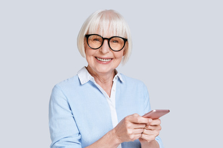 Photo pour Sharing new ideas. Beautiful senior woman using her smart phone and smiling while standing against grey background - image libre de droit