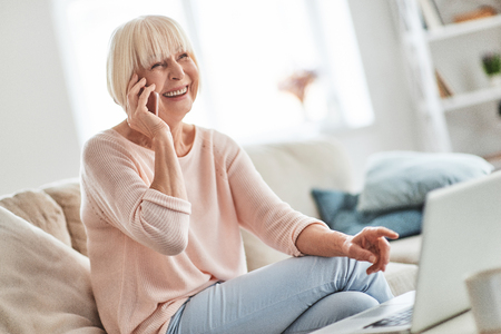 Photo for Happy to hear you! Beautiful senior woman talking on her smart phone and smiling while relaxing on the couch at home - Royalty Free Image