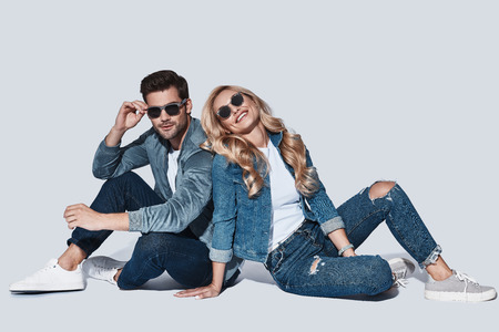 Foto de Pure feelings. Beautiful young couple in denim wear bonding and smiling while sitting against grey background - Imagen libre de derechos