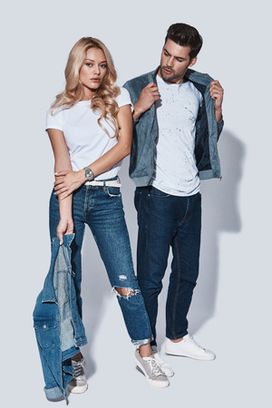 Photo pour Stylish couple. Full length of beautiful young couple bonding while standing against grey background - image libre de droit