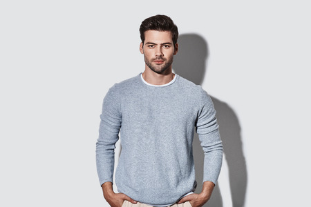 Photo for Perfect man. Handsome young man in casual wear looking at camera and smiling while standing against grey background - Royalty Free Image