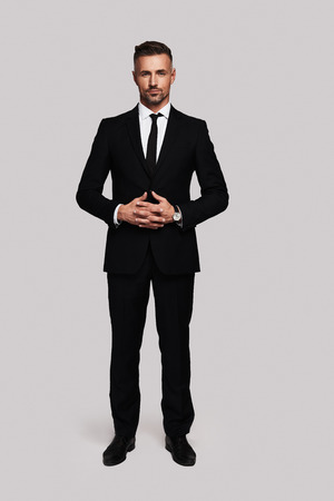 Photo for Business professional. Full length of handsome young man in full suit keeping hands clasped and looking at camera while standing against grey background - Royalty Free Image