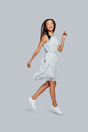 Photo pour Beautiful perfection. Full length of beautiful young Asian woman smiling and looking at camera while standing against grey background - image libre de droit