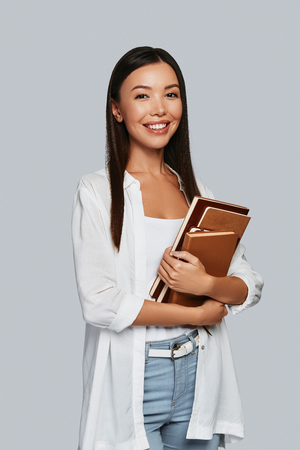 Foto de Intelligence. Beautiful young Asian woman carrying books and smiling while standing against grey background - Imagen libre de derechos