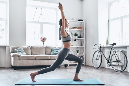 Foto de Staying fit and healthy. Beautiful young Asian woman in sports clothing doing yoga while relaxing at home - Imagen libre de derechos