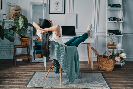 Photo for Total relaxation. Rear view of young woman keeping hands behind head while sitting in home office - Royalty Free Image