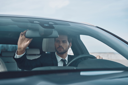Photo for Checking every detail. Handsome young man in full suit adjusting rear-view mirror while driving a car - Royalty Free Image
