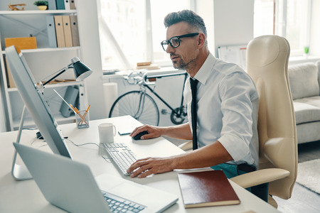Photo for Putting ideas into something real. Thoughtful young man in shirt and tie working using computer while sitting in the office - Royalty Free Image