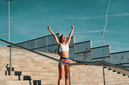 Foto de I did it! Beautiful young woman in sports clothing keeping arms outstretched while exercising outdoors - Imagen libre de derechos
