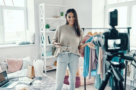 Foto de Beautiful young woman in casual clothing making social media video while spending time at home   - Imagen libre de derechos