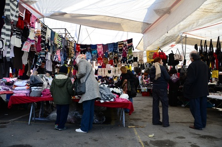 Istanbul, Turkey – November 19, 2011: Turkish people are shopping at local opened air bazaar. Saling goods are more cheaper than shops at this local bazaar.