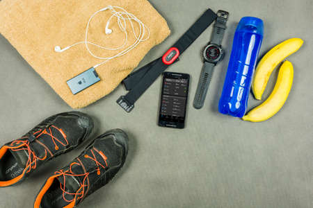 Photo for Niedomice, Poland - June 08, 2018: Runner training equipment. Heart rate monitor (Garmin), an isotonic drink, bananas, a towel, an iPod with dry jackets (Apple) and running shoes (Dynafit). - Royalty Free Image