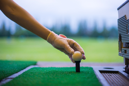 Photo pour Woman golfer's hand holding ball on tee with golf course background. close up of golf players hand placing ball on tee at driving range in sport club. - image libre de droit