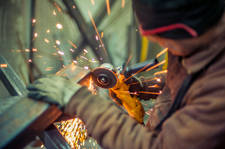 Foto de Electric grinder. A man working with electric grinder tool  on steel structure in factory, sparks flying - Imagen libre de derechos