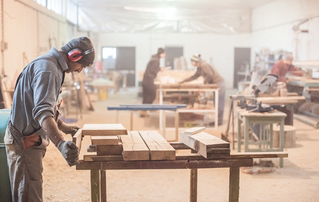 Photo for Man doing woodwork in carpentry. Carpenter work on wood plank in workshop - Royalty Free Image