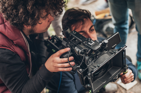 Photo pour Behind the scene. Cameraman and assistant shooting the film scene with camera on outdoor location - image libre de droit