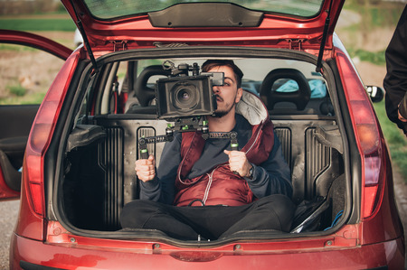 Photo for Behind scene improvisation. Cameraman from trunk of car shooting film scene on outdoor location - Royalty Free Image