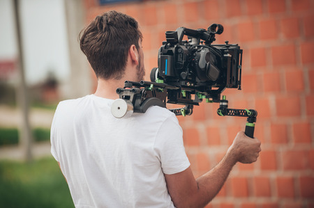 Photo for Behind the scene. Cameraman shooting the film scene with his camera on outdoor location - Royalty Free Image